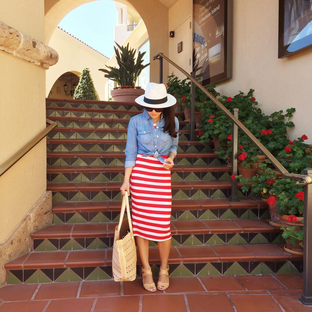 Annie Mai Thai wearing a red and white striped skirt, blue shirt, and white hat.