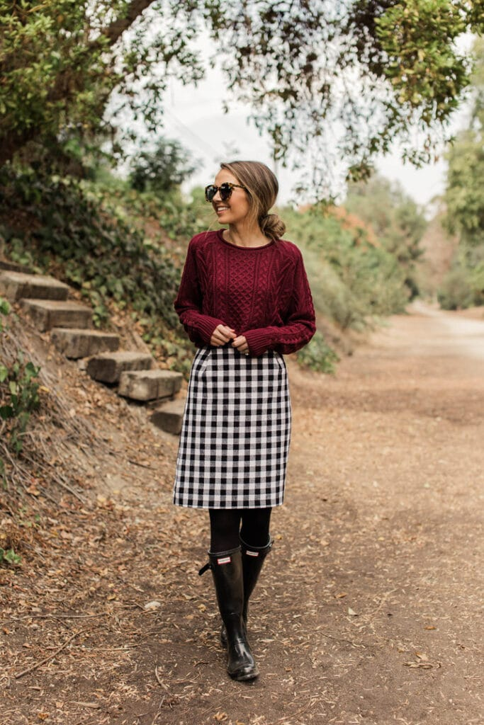 merrick's outfit featuring a buffalo plaid skirt, boots, and maroon sweater