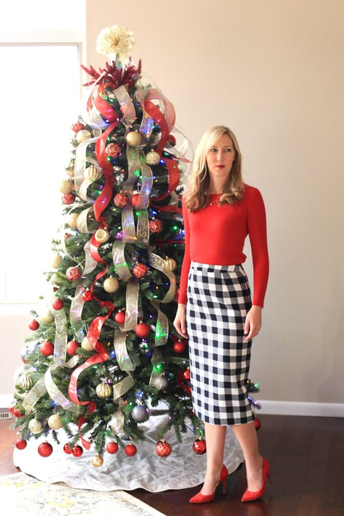 carly's holiday outfit featuring a black and white plaid pencil skirt and red sweater