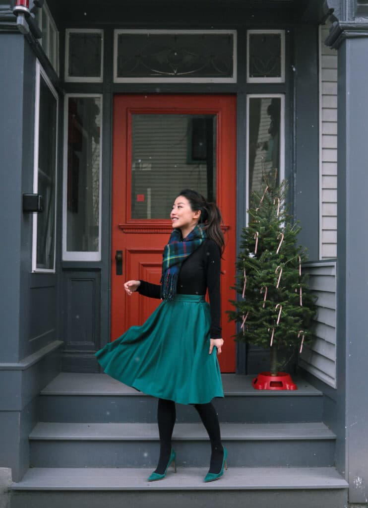 jean wang's christmas outfit with green heels, green skirt, black sweater, and plaid scarf