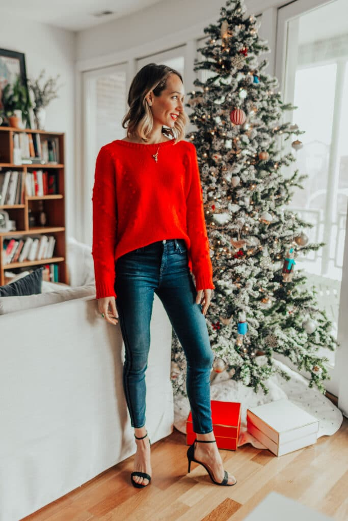 blair staky's festive outfit featuring strappy heels, dark blue skinny jeans, and red sweater