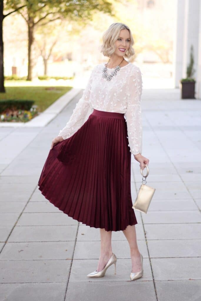 Amy Ann Arnold's holiday look featuring a burgundy midi skirt and sheer blouse.