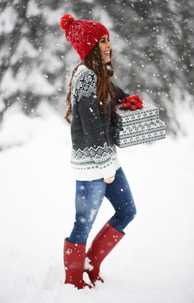 cori's snowy day outfit that has red boots, blue jeans, snowflake sweater, and red beanie