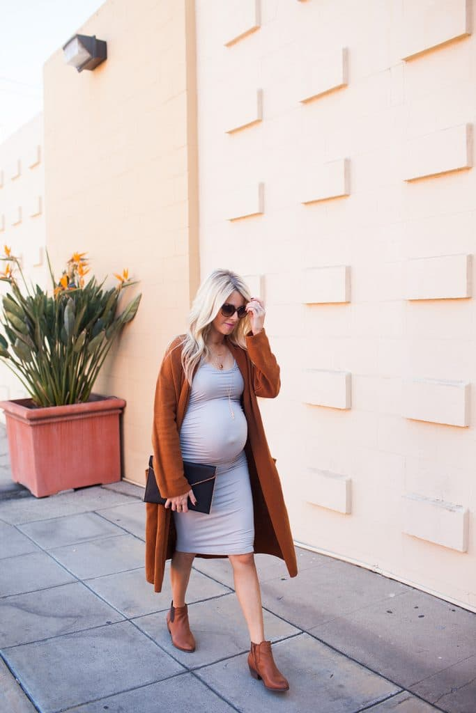 Kailee Wright styles her brown booties with a long cardigan and a light gray maternity dress.