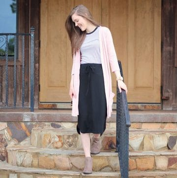 Elizabeth styling an outfit featuring a long cardigan, black, skirt and brown booties