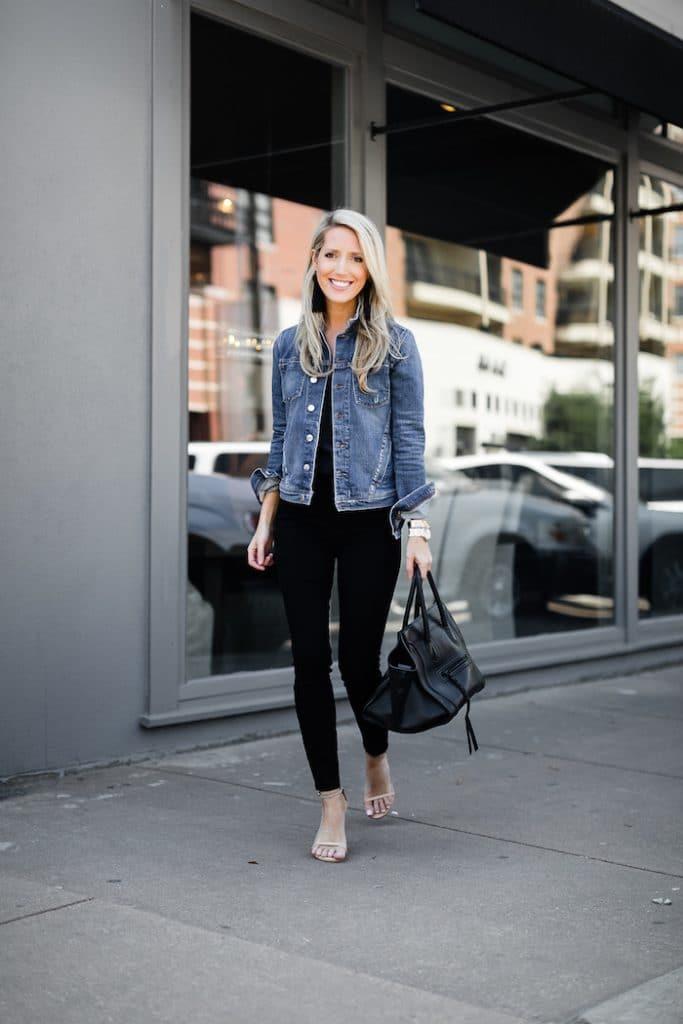 Krystal Davis in a jean jacket, black top, black jeans, and heels.