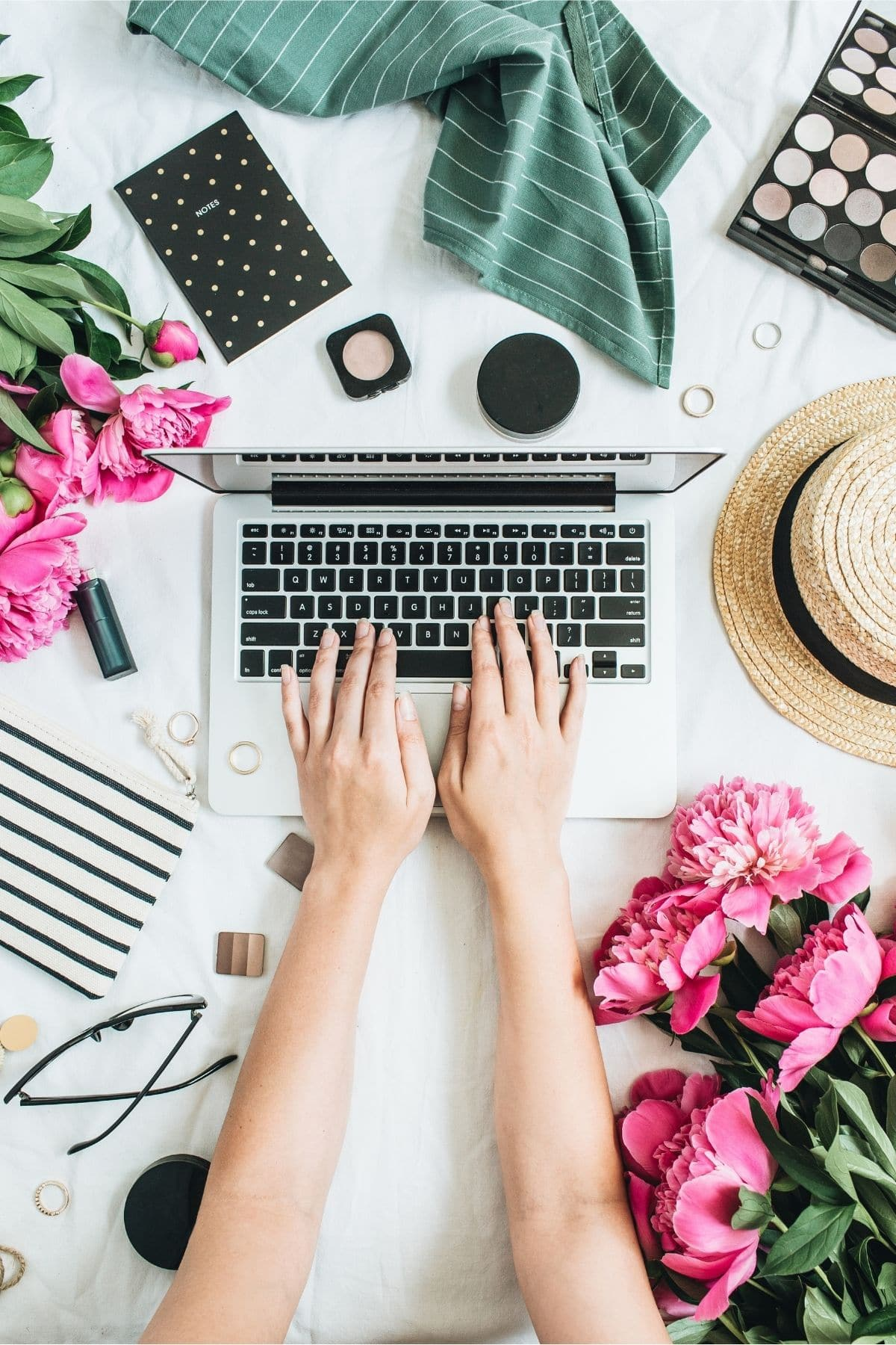 a person's hands and arms reached out touching a computer with flowers, a notebook, makeup, a hat, and more around the laptop