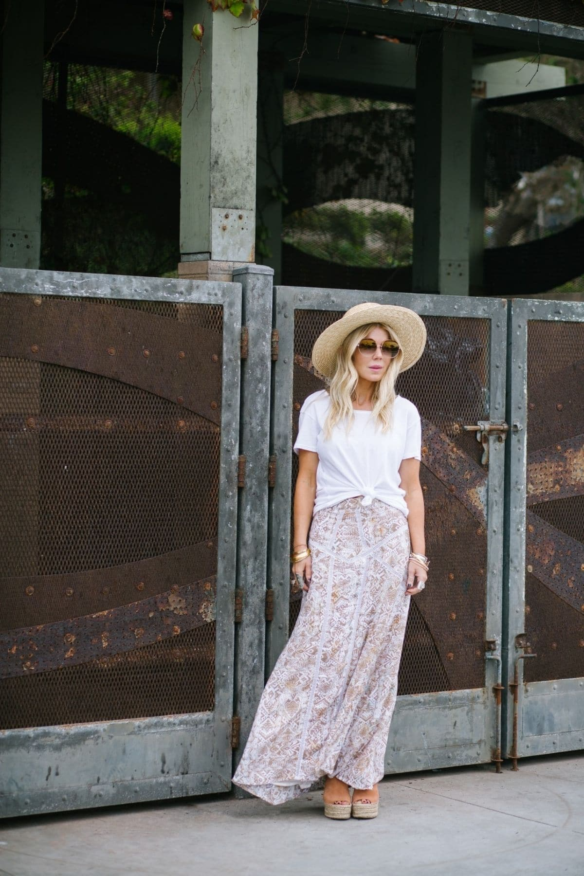maxi skirt outfit with knotted white top, sandals, and straw hat