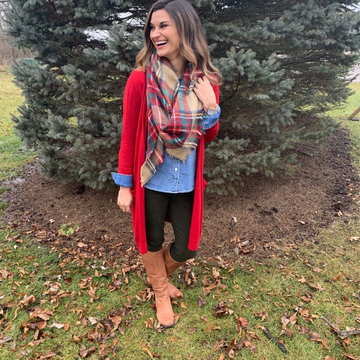 outfit with a scarf over a chambray shirt, red long cardigan, black jeans and tan boots