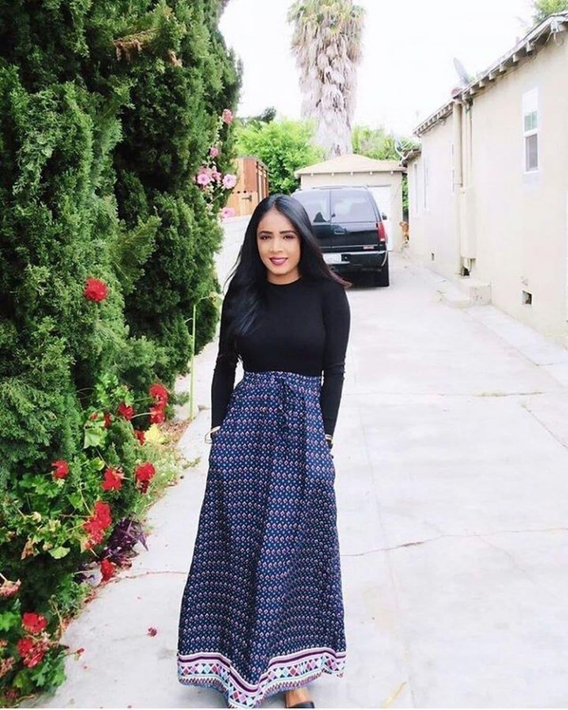 wearing printed long skirt with black long sleeve top