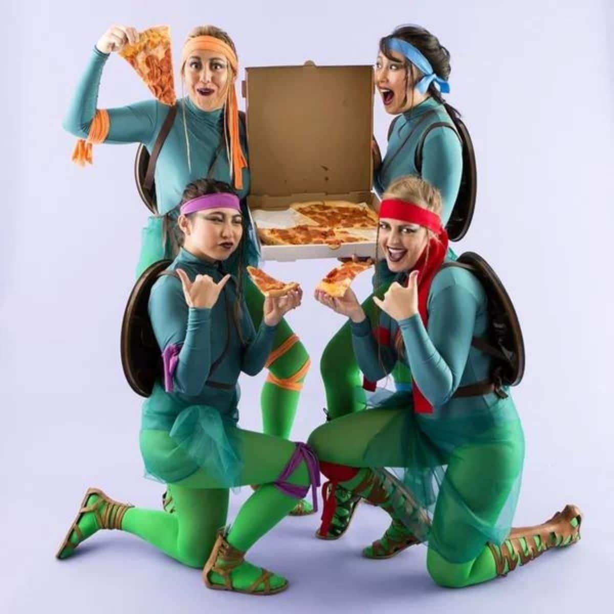 4 girls dressed up as the teenage mutant ninja turtles holding pizza