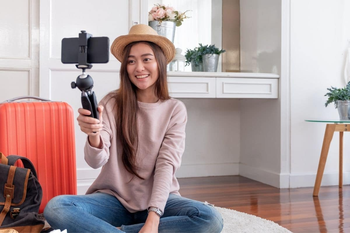 a woman sitting holding a camera and vlogging